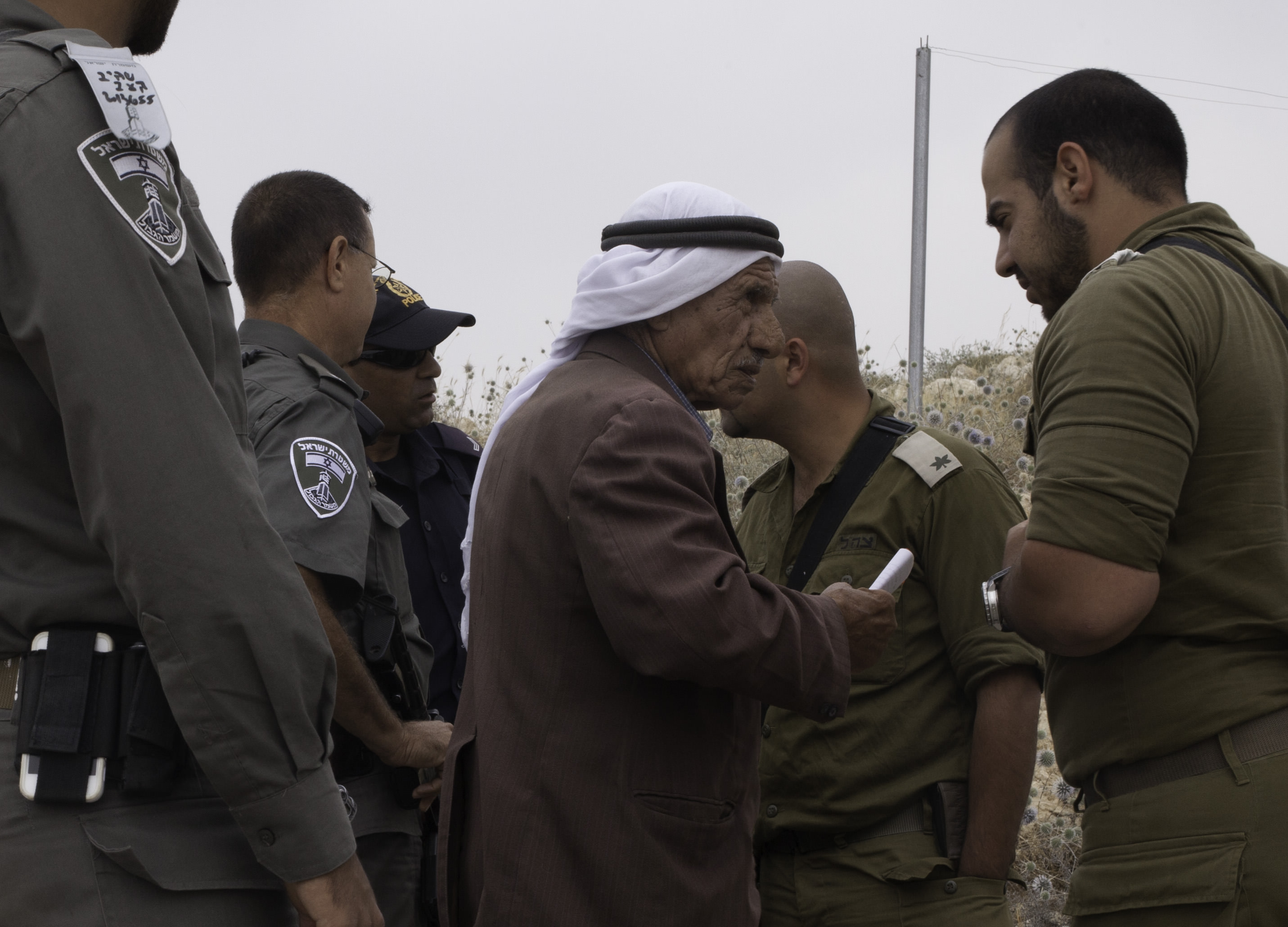 Civil Administration officers surround a Palestinian farmer near Har Mor, an outpost of the settlement Tene. South Hebron, 2014.