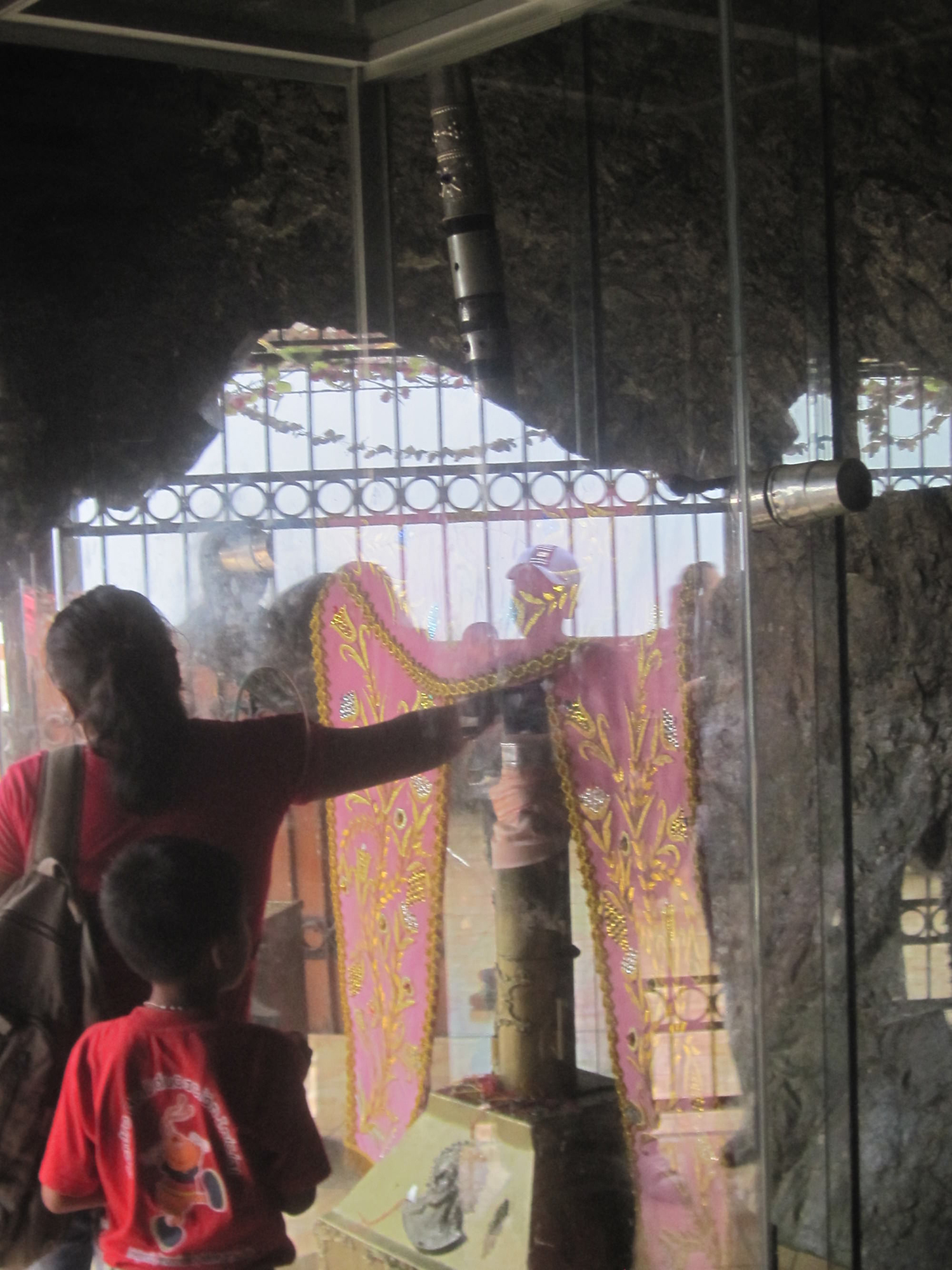 A woman reaches through the glass case to touch the Cross of Motupe