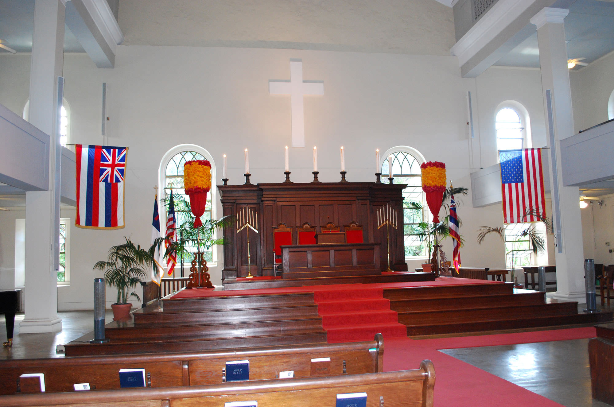 Fig. 10 Kawaiahaʻo Church, Oʻahu, interior, looking toward altar. Note red and yellow royal feather standards; alternating State of Hawaiʻi and United States of America flags flanking sanctuary (flags alternate from front to back and right to left along the full length of the nave); and, left to right, Christian, United States of America, and State of Hawaiʻi flags across front wall under white Latin cross, February 2014. Photo: ©Sally Promey
