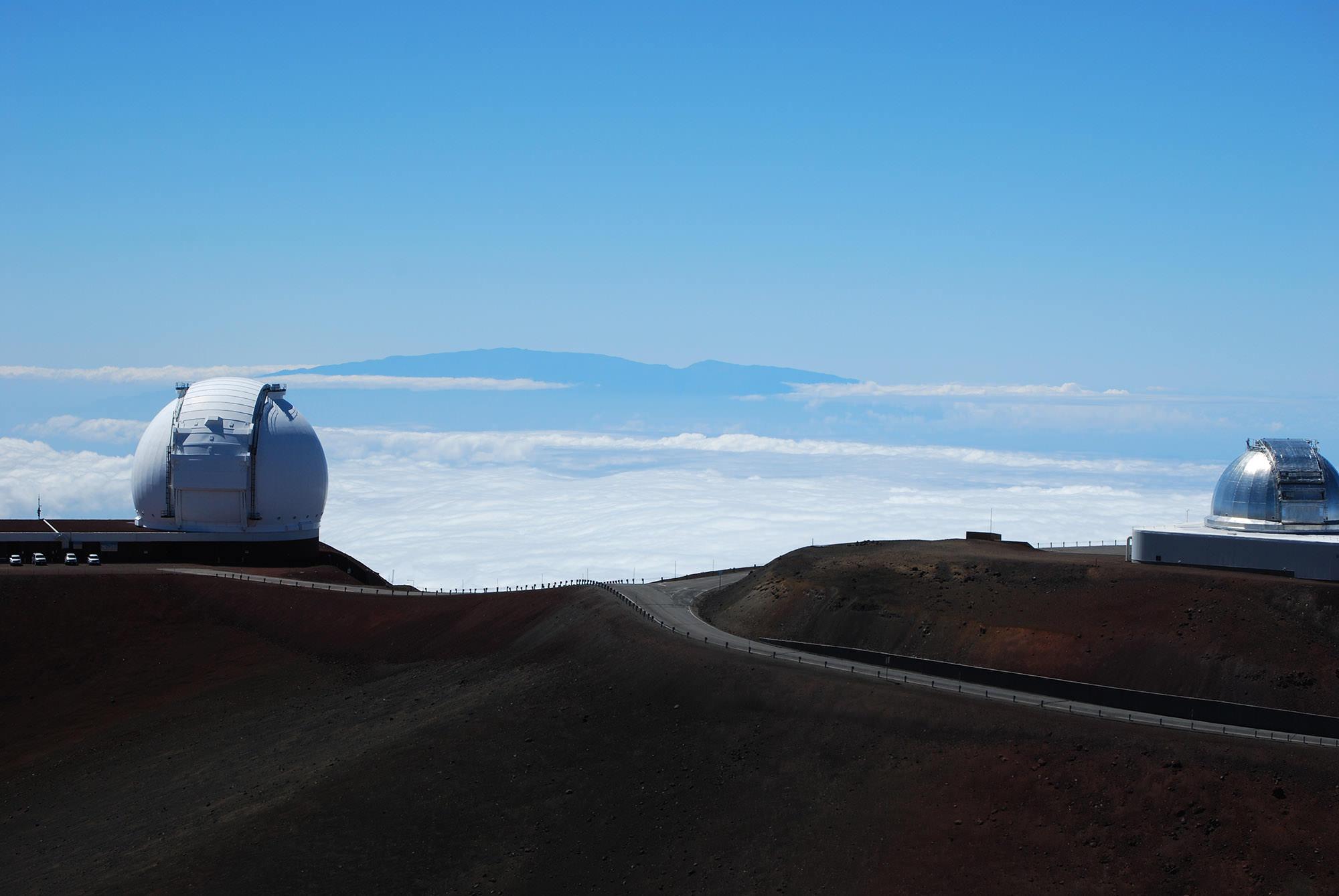 Fig. 18 Summit of Mauna Kea (Mauna a Wākea), Hawai'i Island, showing two observatories, looking toward Haleakala on island of Maui visible in distance, August 2014. Photo: ©Sally Promey