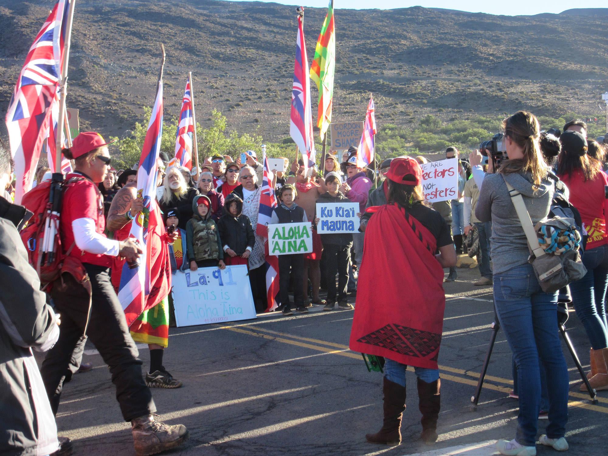 "Fig. 23 Protectors on Mauna Kea (Mauna a Wākea), Hawai'i Island, with signage ""We are Protectors, not Protestors,"" June 2015. Photo: ©Greg Johnson"
