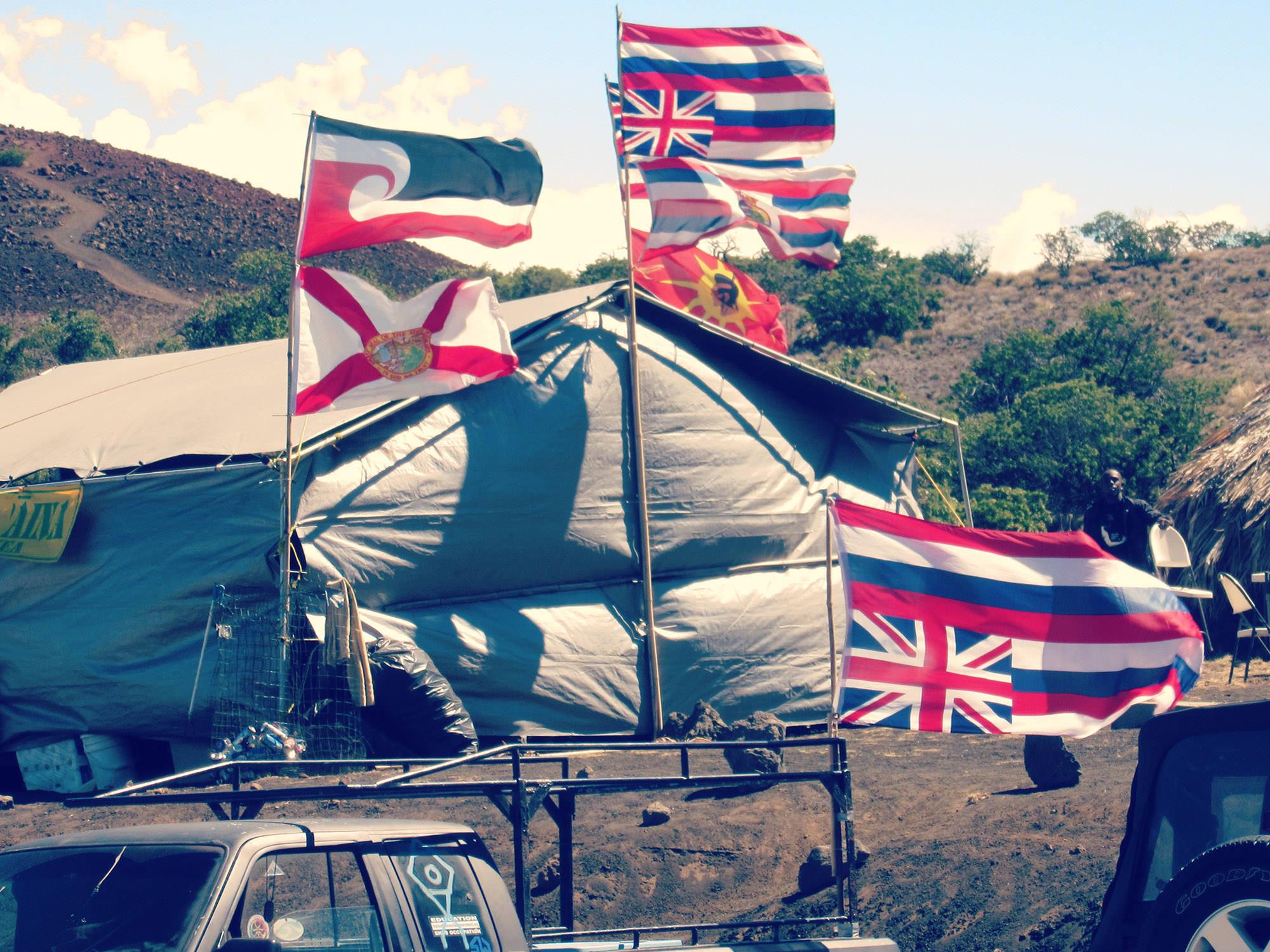 Fig. 24 Protectors camp on Mauna Kea (Mauna a Wākea), Hawai'i Island, flags hung upside-down as signal of distress, June 2015. Photo: ©Greg Johnson