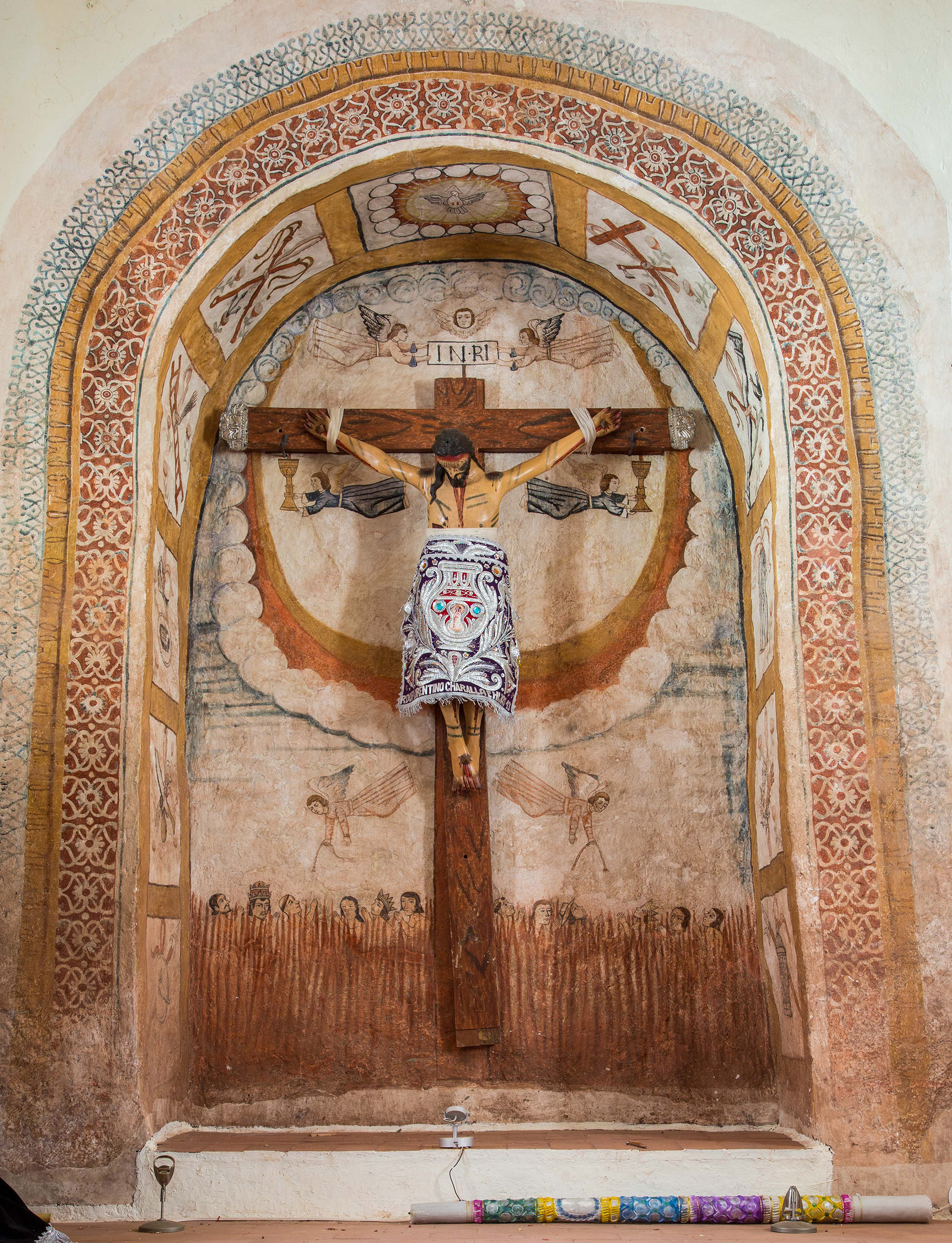 Fig. 31 Painted niche with crucifix, late 18th or early 19th century. Church of Sangarará, Acomayo Province. Photo by Raúl Montero Quispe. This niche incorporates delicate textile designs along the arch and beautifully integrates the crucifix within a painted background with Christ's body set against a heavenly backdrop and the souls of Purgatory below.