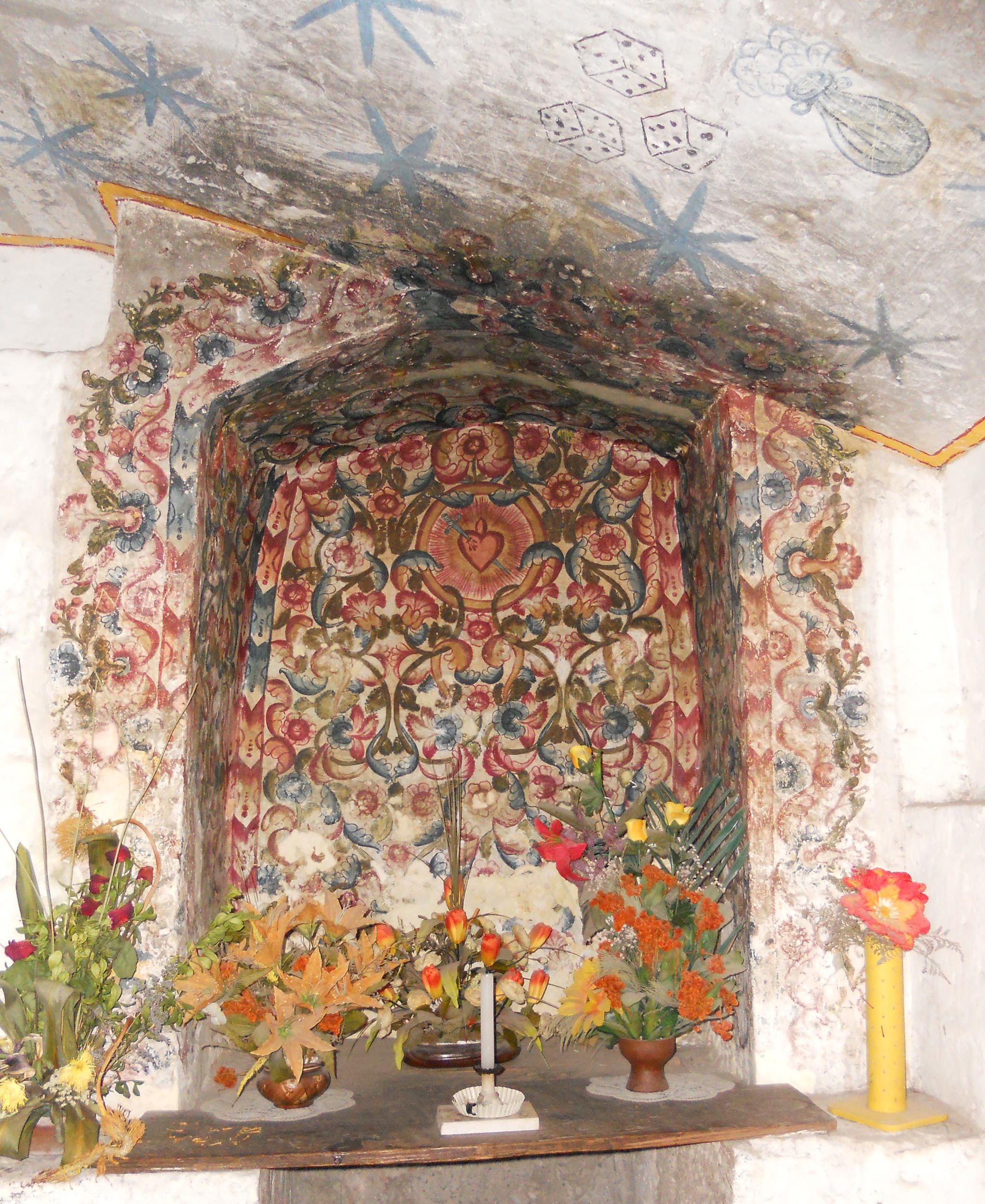 Fig. 6 Niche with painted floral decorations surrounding the Sacred Heart, 18th century, Convento de Santa Catalina, Arequipa. On the ceiling are later mural paintings (probably 19th century) depicting dice, referencing one of the Instruments of the Passion. Photo by author.