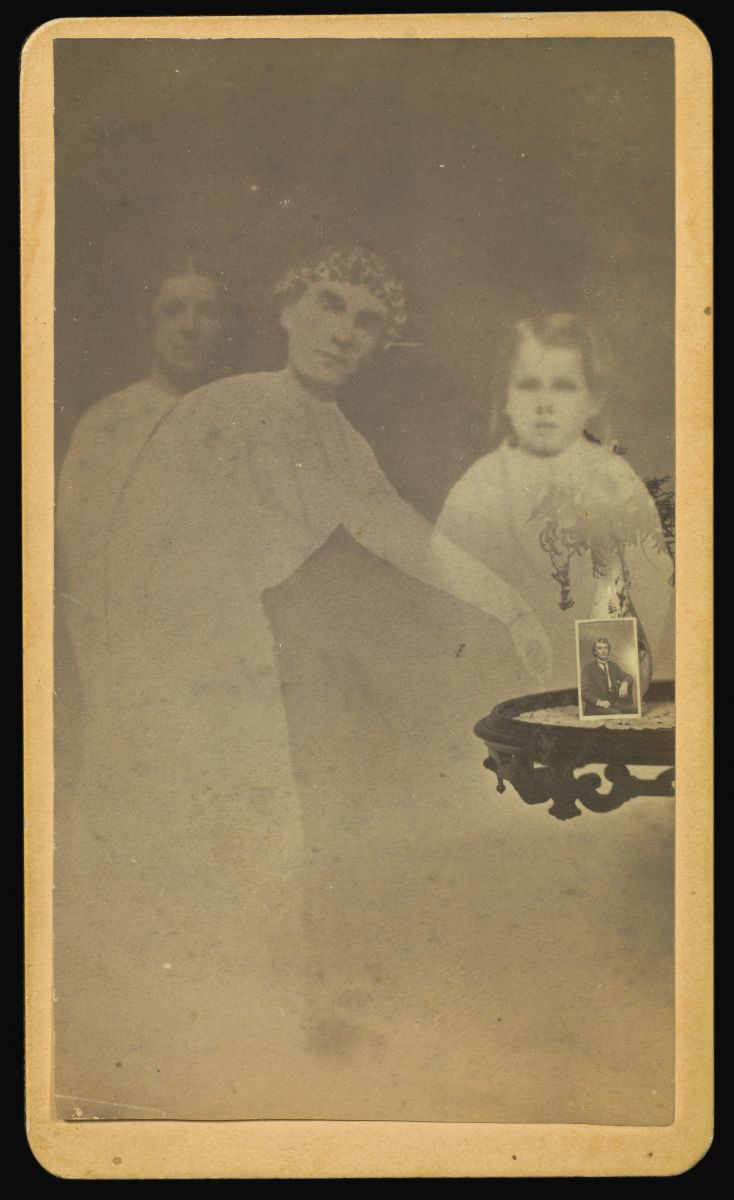 "Fig. 9 William H. Mumler, Three ""spirits"" with a photograph on a table propped against a vase with flowers, albumen silver print, 1862-1875"
