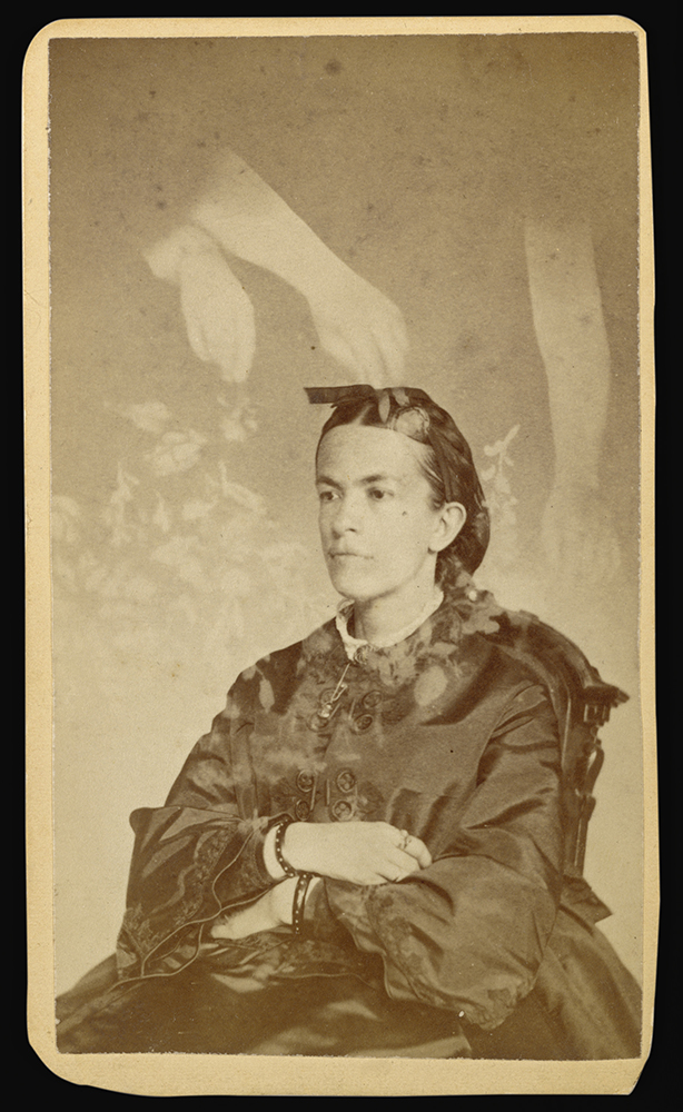 "Fig. 10 William H. Mumler, Unidentified woman seated with arms of a ""spirit"" over her head], Albumen silver print, 1862-1875"