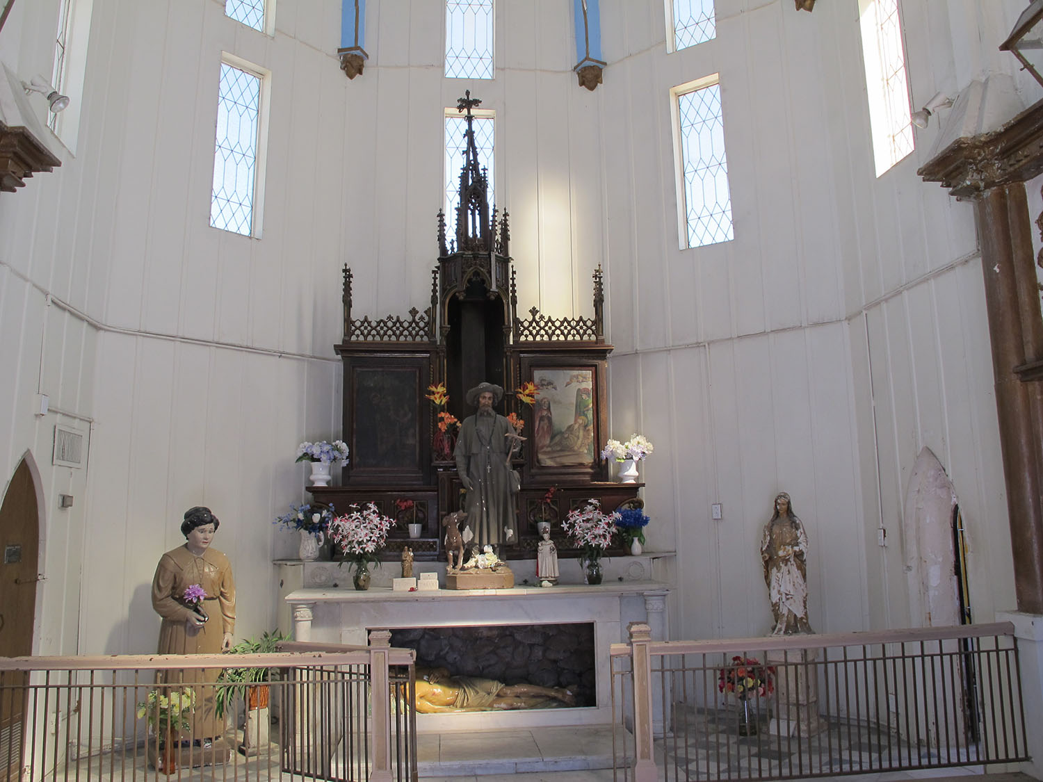 View of the main room of the Shrine of St. Roch with altar and statue of the saint, the door to the small chapel can be seen at the right