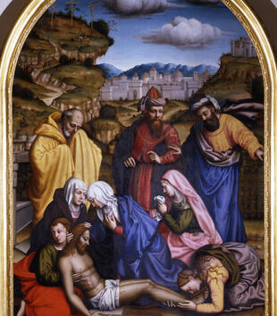 Light-skinned figures in bright drapery gather around a dead figure of Jesus laid on the ground. The group holds up the man's chest, and a woman kneels at his bleeding feet. A green landscape, white buildings, and blue sky form the painting's background.