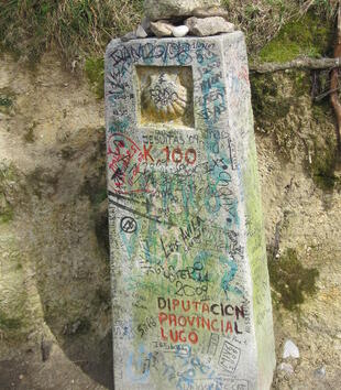 A tall, rectangular marker on the side of the road has been graffitted with inscriptions in many languages and colors. A scallop shell has been carved near the top of the post, and pebbles have been left on top of it.