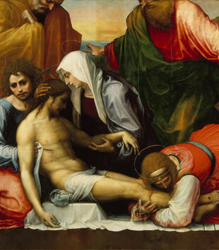 A lamenting group cradles a light-skinned, dead figure of Jesus in this detail of a painting. Two figures hold his head and chest. A woman in a red dress kneels and embraces his feet.