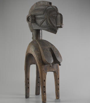 A large wooden figure has an oversized head with carved scarification. Flat breasts with carved, erect nipples and scarification flow over the sculpture's curved, four-legged base. The work's face has large ears and a rounded, protruding nose.