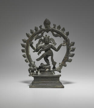 A bronze figure with many arms gestures with his hands and lifts his leg in dance. He is encircled by a ring of flames and stands on a smaller figure. His expression is calm with a slight smile.