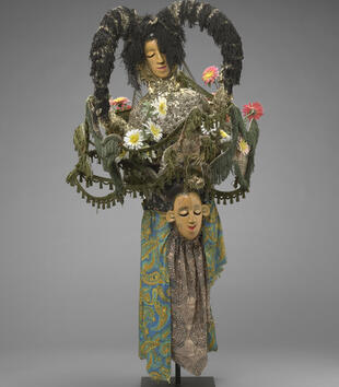 An elaborate mask has two tan-skinned faces embedded in a larger structure of multi-colored fabrics, tassels, and flowers that forms a female figure. She holds a tasseled garland that attaches to the topmost mask. Both faces have almond eyes and red lips.