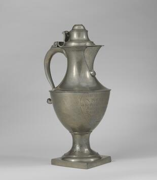 A large metal vessel with a spout and lid has a curved neck atop a bulging body. The front of the vessel is engraved with a German inscription.