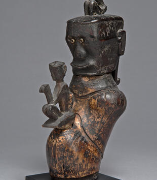 A wooden vessel is shaped like the head and waist of a figure. He has a boxy, square head with circular metal eyes, a rounded nose, and a slightly protruding mouth that curves into a smile. Another, more abstract figure pops out of his chest.