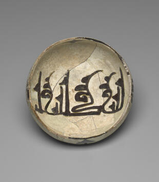 "Painted on a shallow white ceramic bowl is large, black Arabic lettering. The inscription reads, ""God is perfect."""