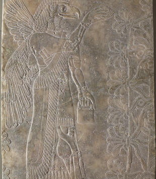 An alabaster bas-relief depicts a standing, eagle-headed figure with wings and human hands. He holds a cone plucked from a tree in one hang and a pail in the other. He wears a frilled robe, jewelry, and other body ornaments.