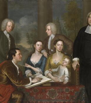 An eighteenth century oil painting depicts a group portrait of light-skinned figures in elegant dress. Sitting at a table are two women with a baby as well as a man writing in a large book with a quill pen. Four other men, including a clergyman, look on.