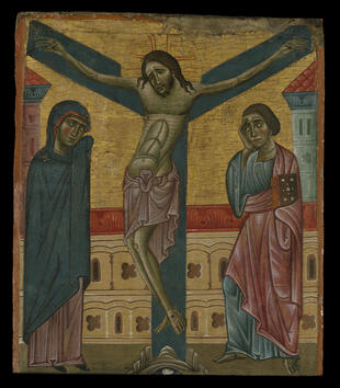 A rectangular panel painting depicts Christ on a blue cross with a V-shaped crosspiece. He has a lithe, curving body. Two figures stands at the foot of the cross, including Mary in a blue veil. Two pastel towers are painted on the gold leaf background.