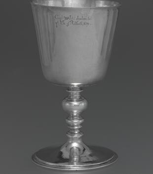 "A silver chalice stands on a baluster stem with a decorative node in the middle of it. The bowl of the chalice is inscribed with small text, ""Capt Willets' donation to ye Ch: of Reliboth, 1674."""