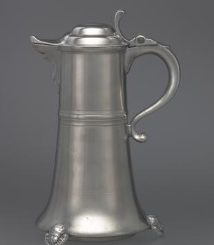 A large silver vessel has a tall body with a curving handle, a lid, and a decorative spout. The flagon stands on four medallions that are carved with the faces of putti, and a midband has been applied at the center.