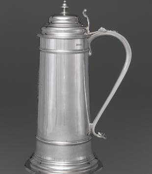 A large silver vessel has a tall straight body with a curving handle and a lid with multiple rings.