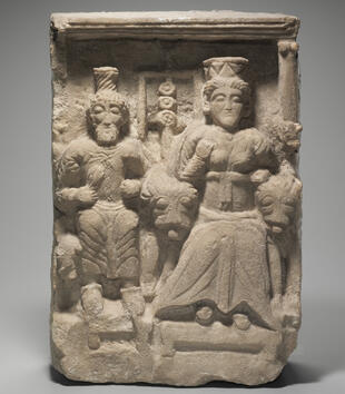 A limestone plaque depicts two figures with cylindrical crowns standing among two lions. One is a bearded man and the other a robed figure. The animals' tongues are carved sticking out of their mouths.