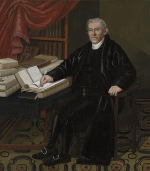 In a painting, a white man in a black waistcoat and flowing robes sits at a desk laden with books. He writes on one with a quill pen. In the background, a red curtain has been pulled to the side to show off a bookshelf.