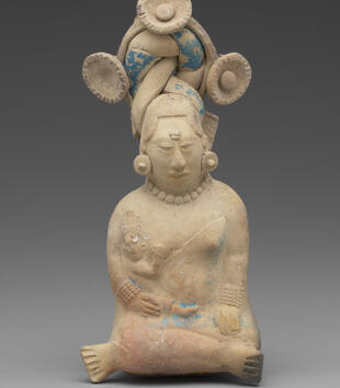 A small clay figurine depicts a woman seated cross-legged with a baby in the crook of her arm. He suckles at her exposed breast. She has on earrings and a ornate headdress with three rosettes and a coiled braid. Remnants of blue paint remain on it.