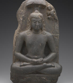 A dark stone sculpture depicts the deity Rishabhanatha. He sits barechested in lotus position with his hands palm up on his lap. The figure has long curling locks of hair. The background is carved to appear like a throne with a small protruding canopy.