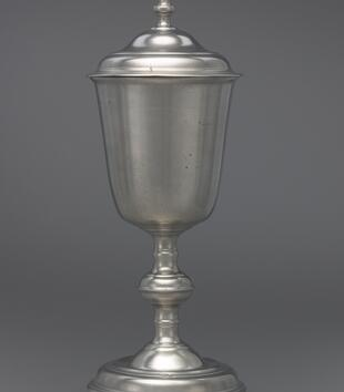 A tulip-shaped, silver chalice has a tall stand with a rounded node in the middle. A silver lid sits on top.