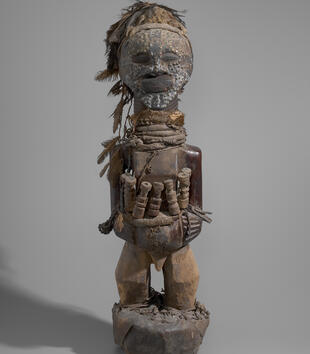 The face of a wooden figure is decorated with small, rounded pieces of brass. The figure wears a feather headdress and its neck is carved with rings. With hands clasped at its abdomen, it cradles smaller human figurines close.