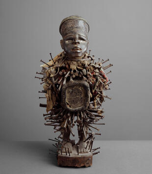 The body of a wooden, male figurine is pierced with many nails. He has a mirrored box in the middle of his abdomen and a face with large, clear features.