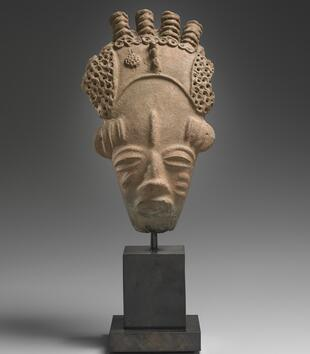 A terracotta head represents a face with almond eyes, an open mouth, a large forehead, and scarring on the cheeks. The head wears a headdress with four ridged knobs on top that is decorated with clusters of small circular rings.
