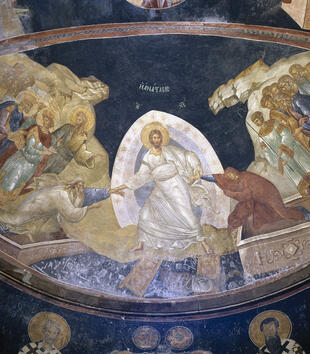 The apse of a church is painted with an image of a white-robed, light-skinned Christ at center. He pulls a man and a woman up out of their graves, which are represented as marble coffins. Other robed figures surround Jesus on either side and look on.