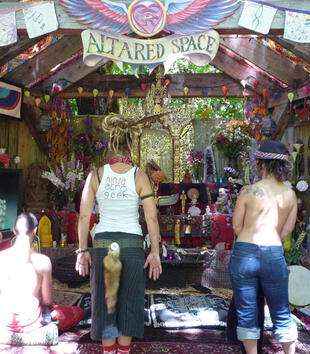"""People are gathered in front of a large, timber-frame structure that has been hung with the whimsical sign, """"ALTARED SPACE"""" and colored banners. Assembled on a tiered structure inside are various religious and spiritual figures, flowers, and cloths."""