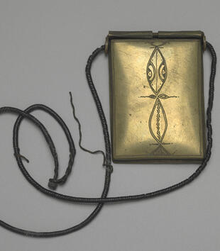 The golden amulet suspended from a leather cord is a carved, rectangular plaque. It is incised with a line of pointed ovals filled with geometric motifs.