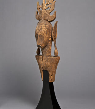 A wooden sculpture depicts the rounded head and square shoulders of a figure. He covers his ears withpaddle-like arms attached to his shoulders. A decorative flame-like plume rises from the top of his head. He has parted lips, a long nose, and round eyes.