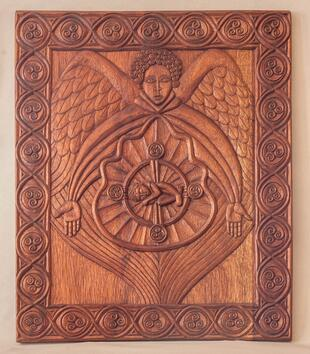 A rectangular wooden frame is carved with a low relief image of a winged figure with his arms outstretch around a mandorla with an infant at its center. The angel has curly hair and wide, geometric eyes. A swirling border is carved around the image.