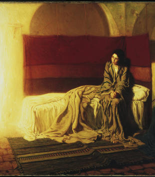 In this painting, the tan face of woman is illuminated by a shiny shaft of light floating in a room. The light fills the room with a wam color. It casts a glow on the woman's flowing gray robe as she sits on a bed of rumpled white blankets and sheets.