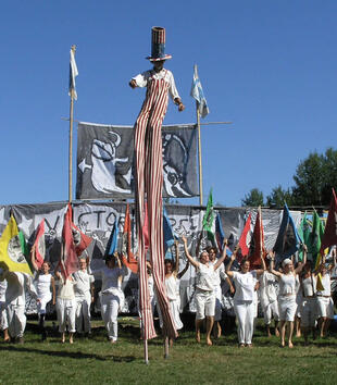 A man on stilts leads a parade of individuals wearing white and holding colorful flags. He wears a long striped jumpsuit and a hat.
