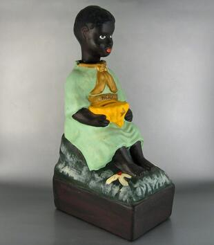 "A plaster figurine depicts a seated dark-skinned young boy in light green dress. It functions as a coinbox via a slot in a basket held by the figure. A banner above the basket reads, ""MERCI."" It has been painted over another inscription ""THANK YOU."""