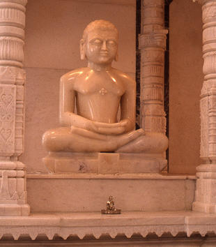 A shiny, light-colored stone statue of a large figure with long earlobes, serene eyes, and a bare chest sits crosslegged and with arms folded. The figure is in an ornately carved shrine of the same stone.