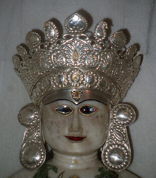 The head of white stone sculpture is crowned with a large, patterned metal crown and oversized earrings.The face has shining glass blue eyes that have black irises and red tips.