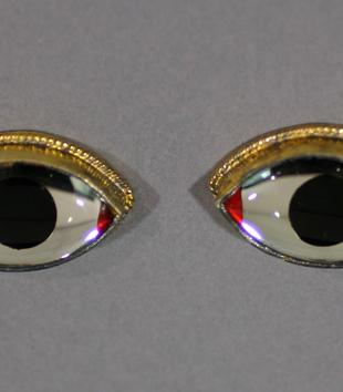 A pair of glass eyes with opaque, dark black irises have red paint at the corners and thin gold rims on top. Each eye has a slightly uplifted wing.