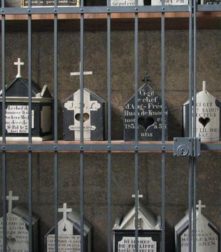Three shelves of small gable-roofed and house-shaped boxes are displayed behind bars. Each box is black and white with a cross affixed to the top. All have text inscribed on the front.