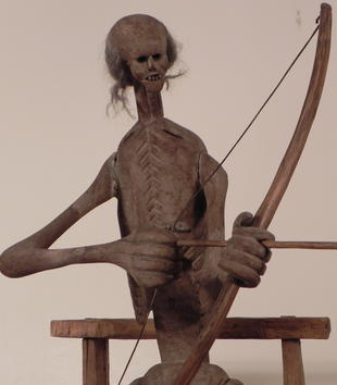 A wooden sculpture depicts a skeletal figure pulling a bow and arrow taunt. He has a flat chest imprinted with ribs, a head of wispy gray hair and large teeth, and oversized hands.