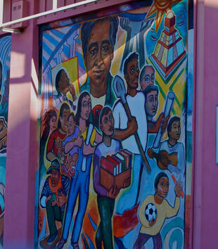 One of the sides of a pink church structure is painted with two colorful mural panels. They depict a diversity of figures of different races and ages. Some hold books, others shovels, and others hold toys.