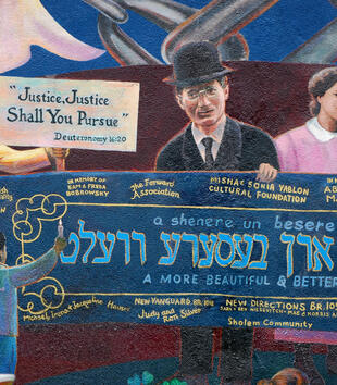 "A mural depicts figures holding a banner inscribed, ""A more beautiful & better world"" in Hebrew, Yiddish, and English. One woman raises her arm in a fist and another holds a sign reading, ""Justice, Justice Shall You Pursue-- Deuteronomy 16:20."""