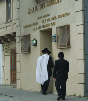 "Two figures enter a pale building with gold lettering, ""KOLLEL LOS ANGELES."" One man wears a wide-brimmed black hat, a white tallit, and a black suit. A younger boy wears a suit and a yarmulke."